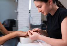 Woman manicurist trims cuticles on the nails of client. Stock Images