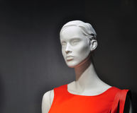 Woman mannequin, fashion shop. Portrait of woman mannequin in red in a shop window, commerce and business Stock Images