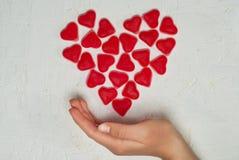 Woman& x27; mano di s con cuore fatto dalla gelatina di frutta Fotografie Stock Libere da Diritti