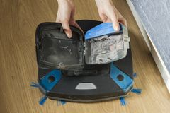 Woman& x27; manos de s remooving un envase del polvo del aspirador robótico fotografía de archivo libre de regalías