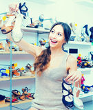 Woman with many chosen shoes. Positive young girl standing in store with many chosen shoes in hands stock photos