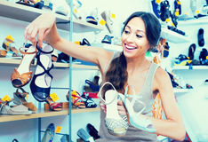 Woman with many chosen shoes. Positive young woman 30s standing in boutique with many chosen shoes in hands royalty free stock photo