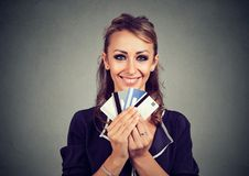 Woman with many different credit loyalty discount cards. Isolated on gray wall background Royalty Free Stock Images