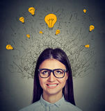 Woman with many ideas light bulbs above head looking up. Young woman with many ideas light bulbs above head looking up isolated on gray wall background. Eureka Stock Images
