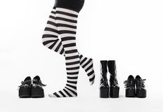 Woman with many shoes. Closeup of a woman leg on floor and many shoes around royalty free stock photo