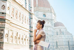 Woman with map and audio guide in florence, italy. Happy young woman with map and audio guide in front of cattedrale di santa maria del fiore in florence, italy stock photography