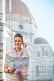 Woman with map and audio guide in florence, italy. Portrait of happy young woman with map and audio guide in front of cattedrale di santa maria del fiore in royalty free stock photography
