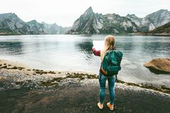 Woman with map and backpack planning route. Sightseeing Lofoten islands in Norway solo travel lifestyle concept adventure outdoor summer vacations Royalty Free Stock Images