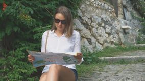Woman with a map. Blonde woman with map sitting in the park stock video footage