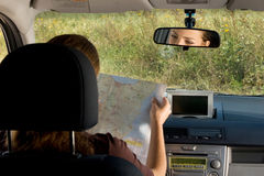 Woman with map in the car. Royalty Free Stock Images