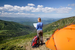 Woman with map exploring in the mountain Stock Images
