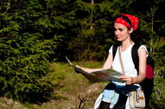 Woman with a map in forest. Woman orientating with a map in forest Royalty Free Stock Photos
