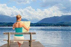 Woman with map on a lake Royalty Free Stock Photo