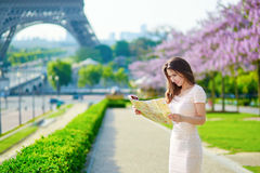 Woman with map near the Eiffel tower in Paris. Young beautiful female tourist with map near the Eiffel tower in Paris, looking for the direction Stock Photo