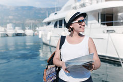 Woman with map near luxury ships Stock Photos