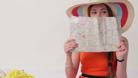 Woman with map near suitcase. Surprised lady looks at map. Planning the route of trip. Far from the country's borders stock footage