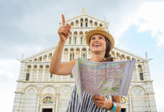 Woman with map pointing in front of duomo di pisa, Stock Photo
