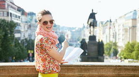 Woman with map pointing on statue at Wenceslas Square in Prague. Catch the spirit of old Europe in Prague. Smiling young woman in sunglasses with a map standing Stock Images