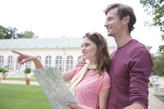 Woman with map showing something to man against building Royalty Free Stock Photo