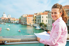 Woman with map standing on bridge in Venice Stock Image