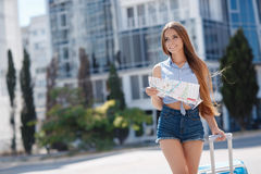 Woman with map and suitcase in city street. Stock Photos