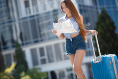 Woman with map and suitcase in city street. Stock Image