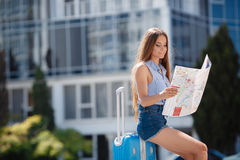 Woman with map and suitcase in city street. Stock Photography