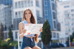 Woman with map and suitcase in city street. Royalty Free Stock Images