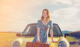 Woman with map and suitcase near a yellow car Stock Photography