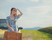 Woman with map and suitcase near a yellow car Stock Image
