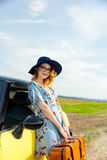 Woman with map and suitcase near a yellow car Royalty Free Stock Photos