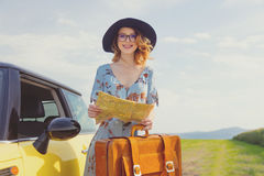 Woman with map and suitcase near a yellow car Royalty Free Stock Photo