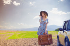 Woman with map and suitcase near a yellow car Stock Photos