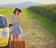 Woman with map and suitcase near a yellow car Royalty Free Stock Photography