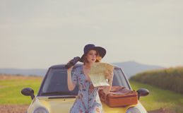 Woman with map and suitcase near a yellow car Royalty Free Stock Images