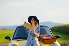 Woman with map and suitcase near a yellow car Royalty Free Stock Image
