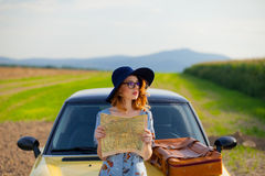 Woman with map and suitcase near a yellow car Stock Photo
