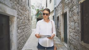 Woman with a map. Young blonde woman with a map in the street stock video footage