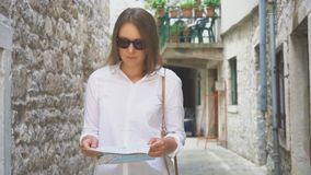 Woman with a map. Young blonde woman with a map in the street stock footage