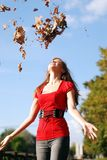 Woman and maple leaf. Young happy woman in red throw the maple leaf royalty free stock photography
