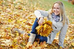 Woman with maple leaves at autumn Royalty Free Stock Images