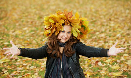 Woman with maple wreath at autumn outdoors Stock Photos
