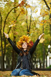 Woman with maple wreath at autumn outdoors. Smiling young woman with outstretched arms and autumn maple leaves wreath in park at fall outdoors royalty free stock photo