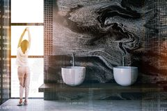 Woman in marble bathroom with sinks. Rear view of woman in pajamas standing near window in luxury bathroom interior with black marble walls, concrete floor and royalty free stock photography