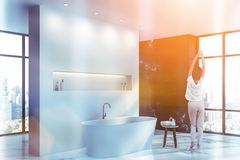 Woman in marble bathroom with tub stock images