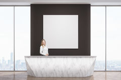 Woman at marble reception desk. Portrait of a businesswoman standing at a marble reception desk with a square poster hanging on a black wall behind her. 3d Stock Photos