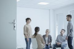 Woman during marital therapy. Woman standing in front of a men during marriage therapy with mediator in white office Stock Photos
