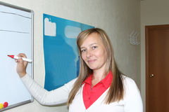 The  woman with a marker standing at a board. The young woman with a marker standing at a board Royalty Free Stock Photo