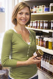 Woman in market looking at preserves smiling Stock Image