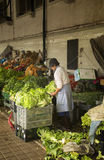 Woman in a market preparing lettuce Royalty Free Stock Images